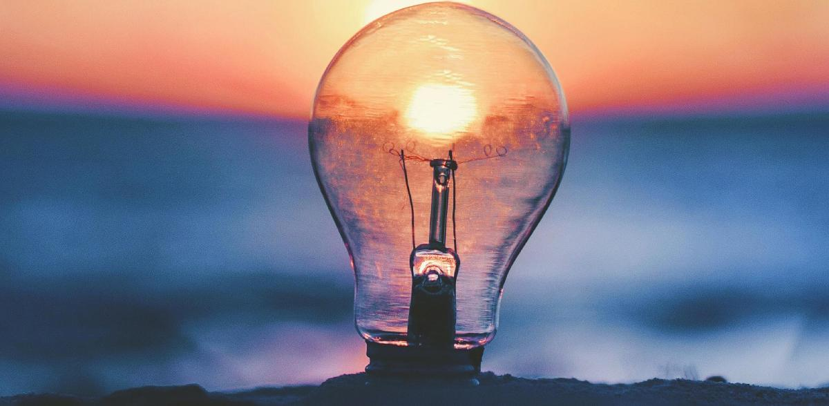 A light bulb buried in sand against a blurred background of a sunset on the sea