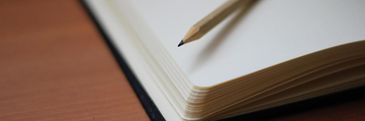 A notebook with blank white pages looked at an angle with a wooden, pointy pencil on top of it
